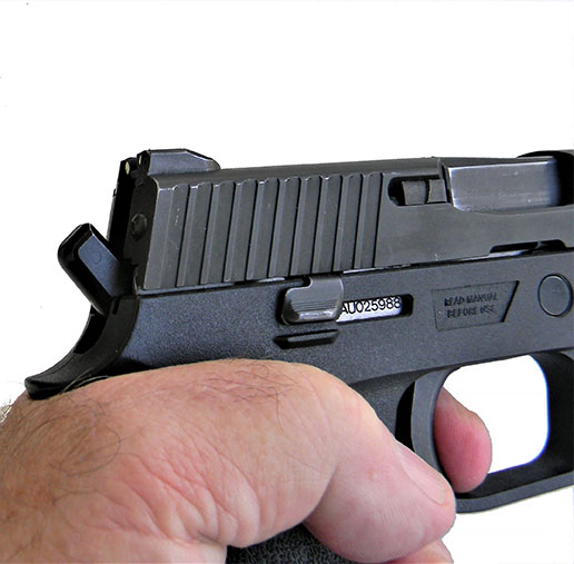 SIG P250 handgun with the trigger depressed enough to expose the hidden hammer