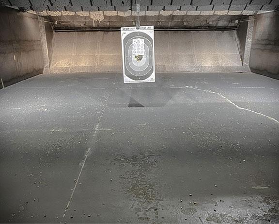 paper target hanging in an indoor shooting range for new shooter
