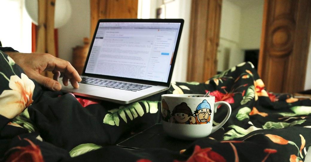 Mit Macbook und Kaffeetasse im Bett
