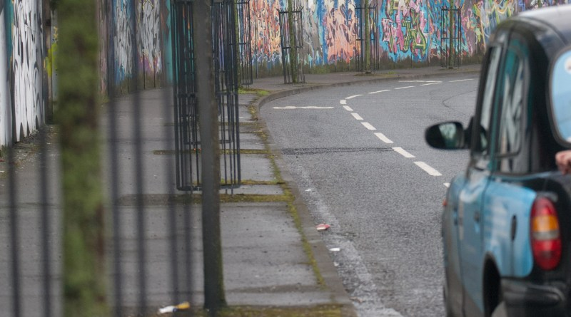 Black cab parked by murals on the Peace Wall in Belfast