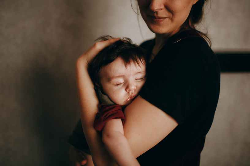 crop mother with sleepy baby in arms