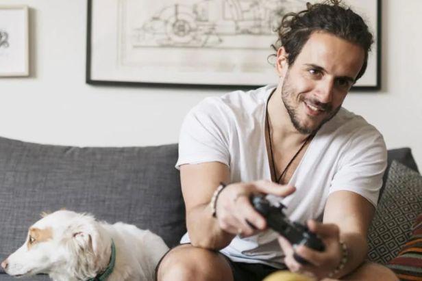 Hombre jugando videojuegos con perro al lado