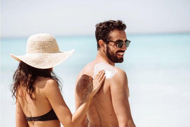 Hombre y mujer joven en playa usando protector
