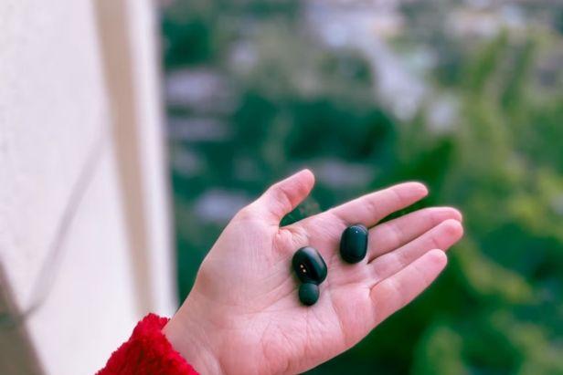 mano sostiene audífonos bluetooth - claro Shop