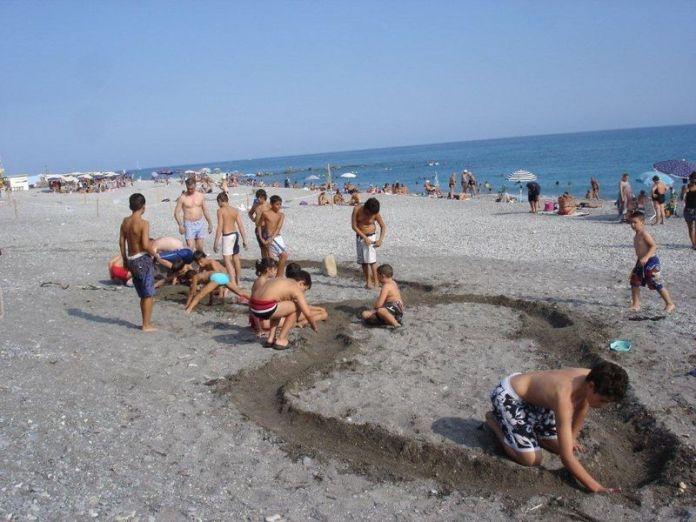giochi da spiaggia: bambini fanno gara di biglie