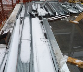 Snow and ice cover the construction materials.