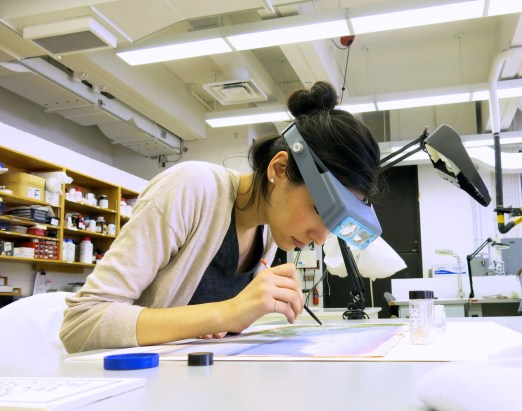 Intern Laura Hashimito uses magnification to inpaint a watercolor work of art on paper after removing staining that disfigured the image area at Queen's University, 2015.