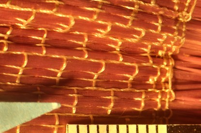 Photomicrograph of the doll (77.4.89) showing use of organic threads (white) and glass fibers (lavender/pink).