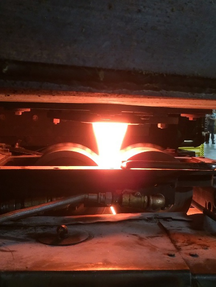 Molten glass sags through an opening to form a ribbon of glass.