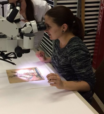 Photograph of Colette looking through a microscope at a print