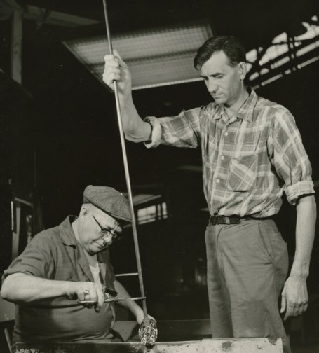 Photograph of a gatherer and gaffer working together on a piece of glass