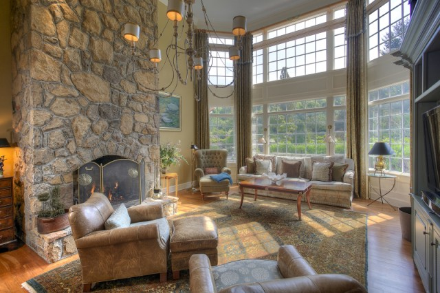 Warm up your toes by the fire and bask in the warm glow of the sunlight streaming in from the floor to ceiling windows of this Mendham, NJ great room.