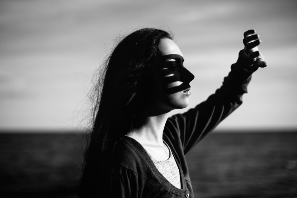 Real young girl in casual wear illuminated by the setting sun near the sea with her hand covering her face from sun light. black and white