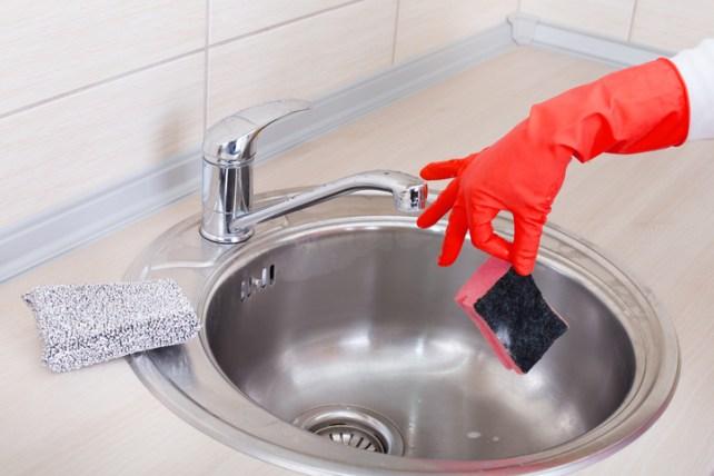 Hand with sponge above kitchen sink