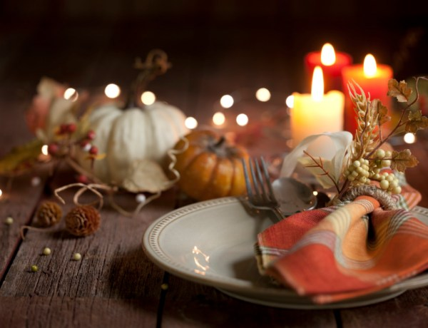 Wood table with place setting, orange candles, and pumpkins