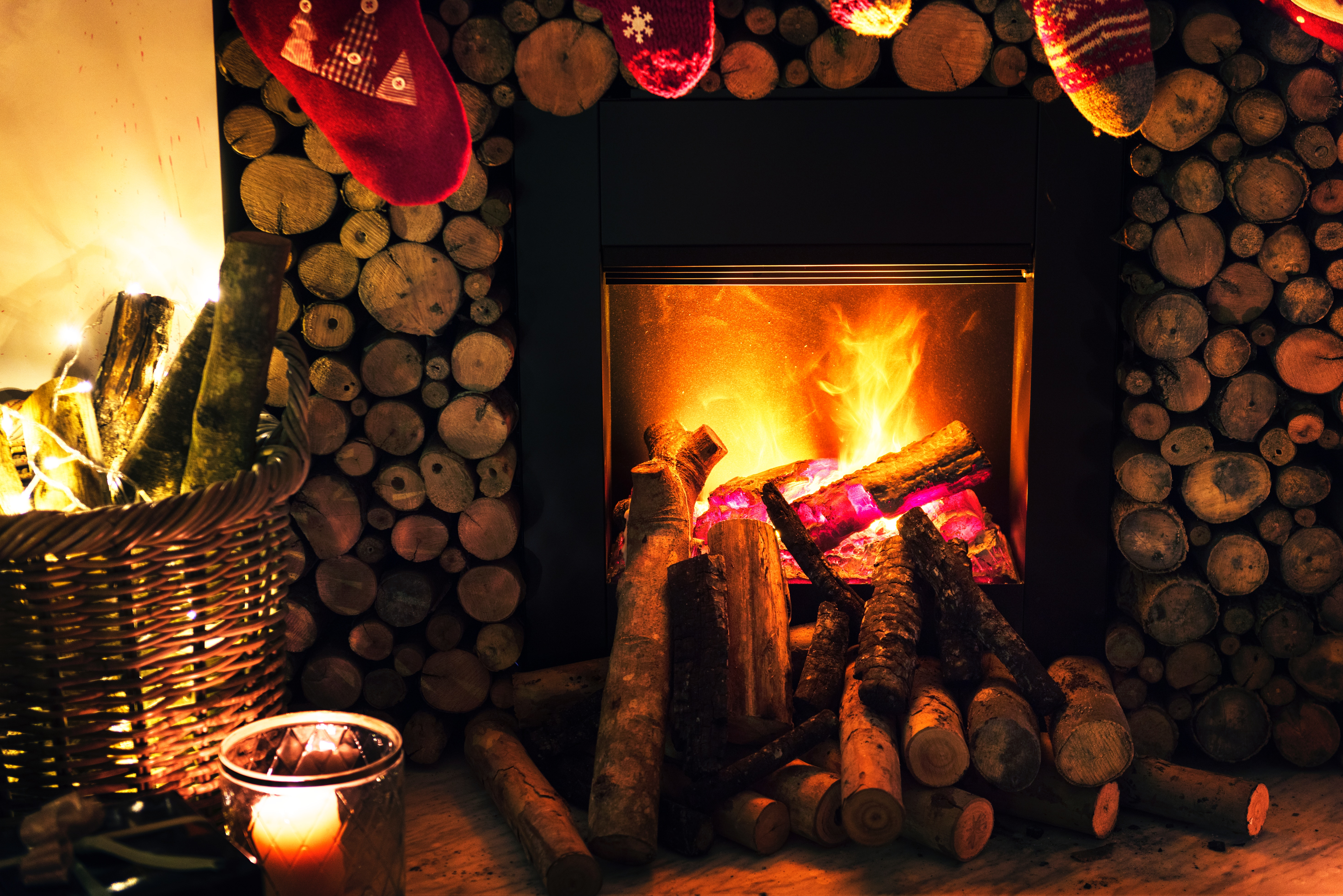 Fire in fireplace with Christmas stockings hung from mantle