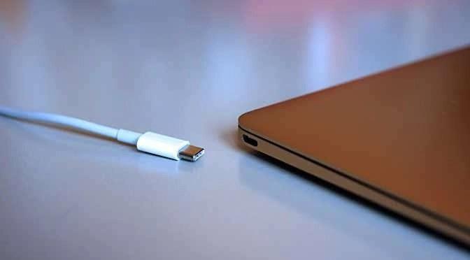 Een USB-C plug en connector op de laptop (bron afbeelding: https://commons.wikimedia.org/wiki/File:Apple_MacBook%27s_new_USB-C_(Type-C)_port_(17182398859).jpg)
