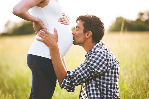 Young man kissing the belly of his pregnant woman