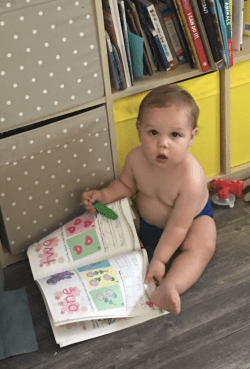Baby in stellar diaper reading a book