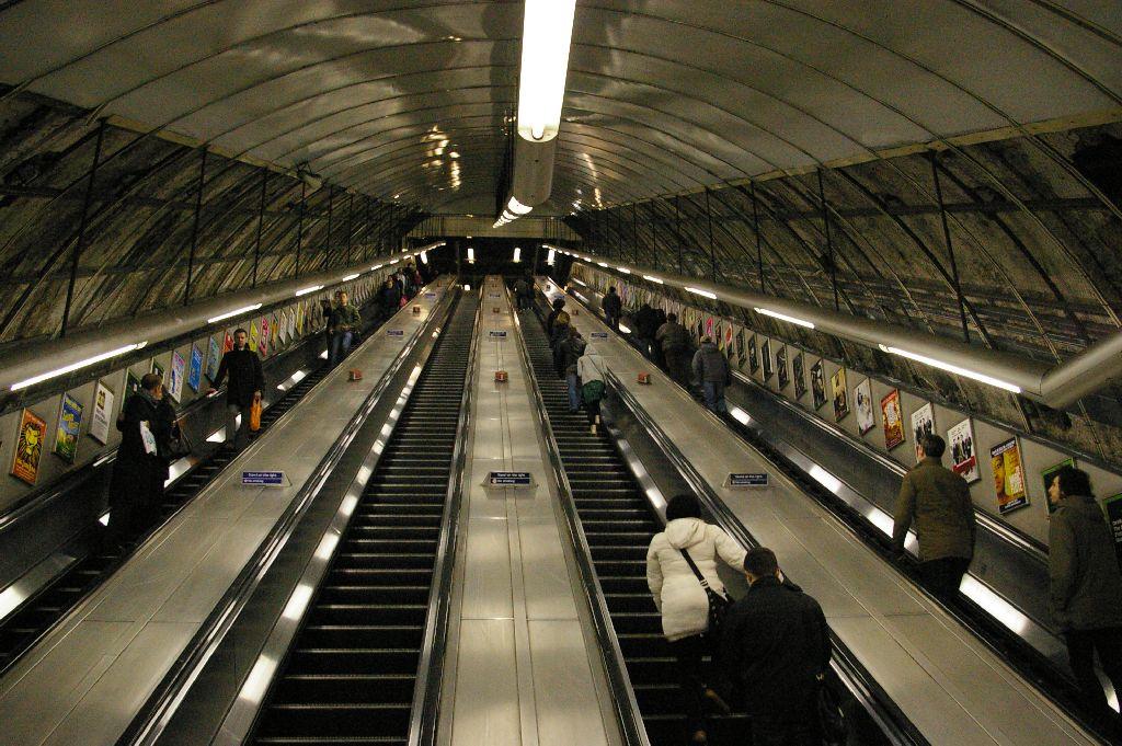 "https://commons.wikimedia.org/wiki/File:Holborn_Tube_Station_Escalator.jpg - Creative Commons - ""Holborn Tube Station Escalator"" by renaissancechambara"