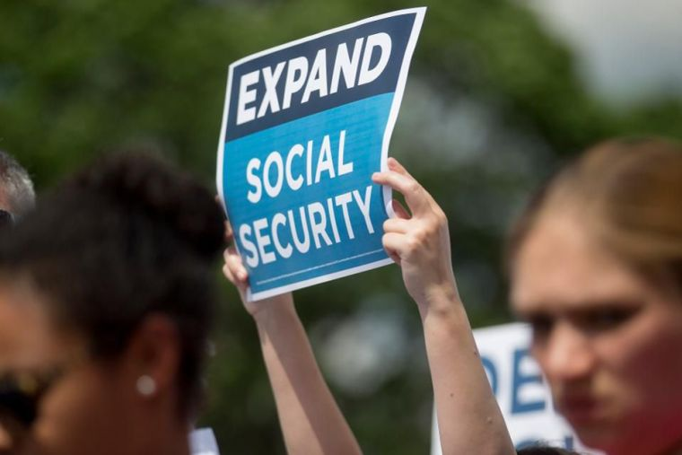 Woman holding sign at protest that says expand social security