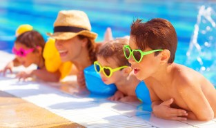 Happy family in the pool, having fun in the water, mother with three kids enjoying aquapark, beach resort, summer holidays, pleasure concept
