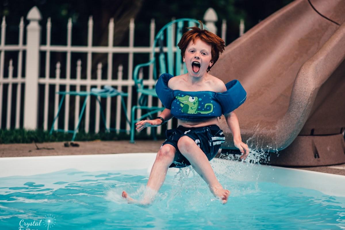 Little boy sliding on pool slide in Nashville