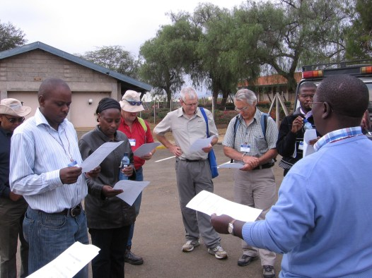Local Africans and foreign scientists stand in a carpark reading pieces of paper