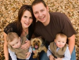 A couple with two small children and a dog sitting amongst autumn leaves