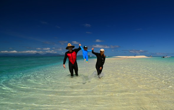 Family swinging chilld walking through shallow water on the Great Barrier Reef