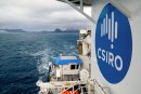 View from top of ship with islands in background and large circualr blue and white CSIRO logo in foreground