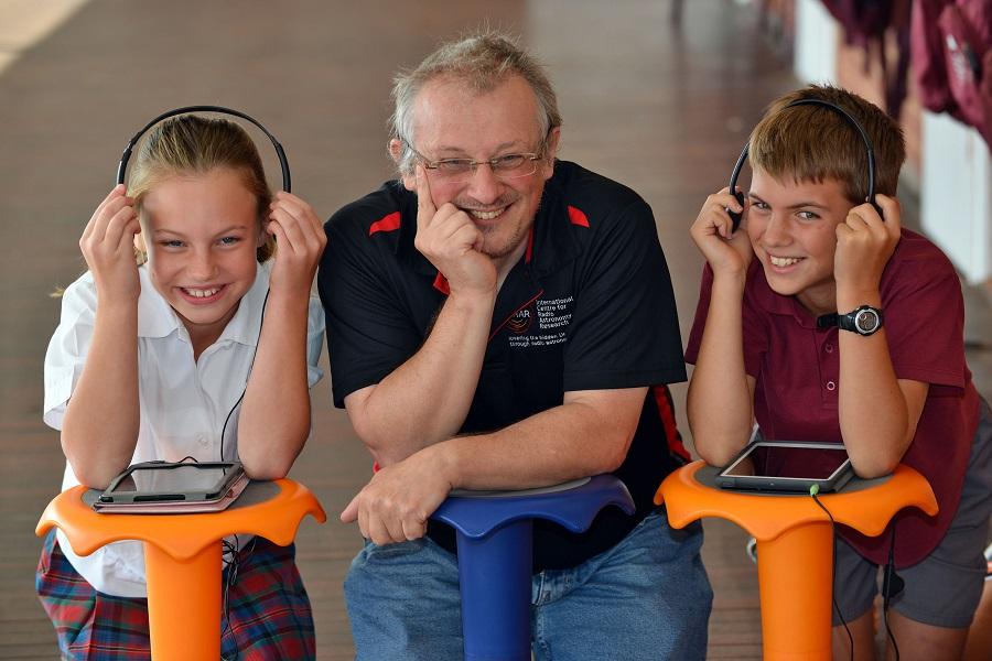 STEM volunteer working with primary school students with audio equipment