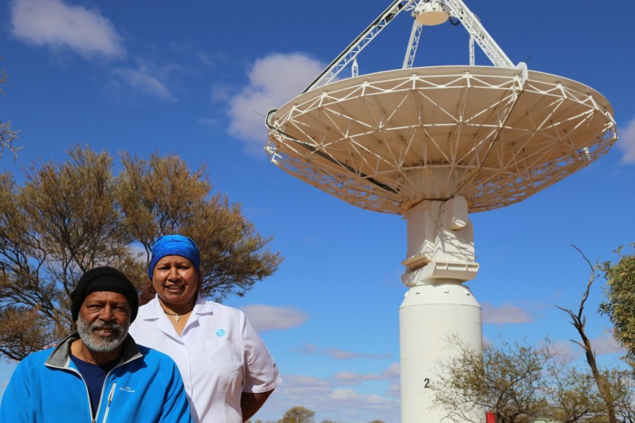 Mr Ernie Dingo and Ms Leonie Boddington, our Aboriginal Liaison Officer, under one of the ASKAP antennas at the Murchison Radio-astronomy Observatory.