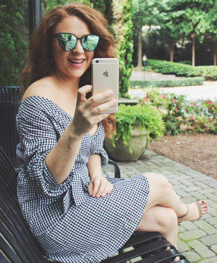 Katherine laughs taking a picture on her phone