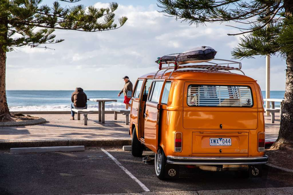 orange van parked in front of ocean view
