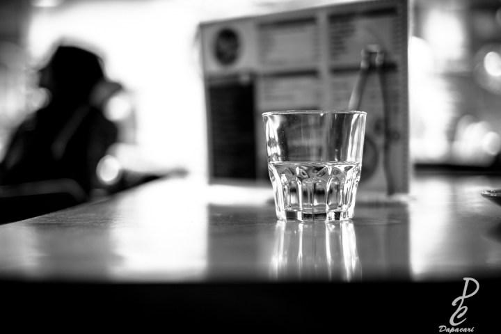 photo en noir et blanc dans un barre mise au point sur un verre le reste est flou avec une personne à gauche semble être entrain de se reposer
