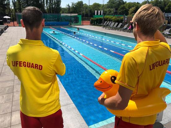 Image of two lifeguards looking out over the outdoor pool.