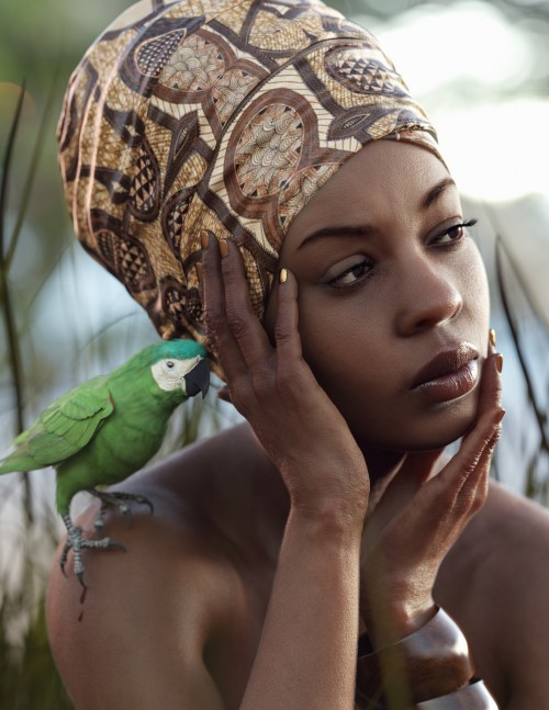 a woman looking off to the side with a bird perched on her shoulder