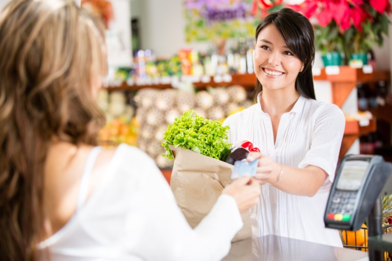 A grocery store cashier hands back credit card to a smiling customer who is holding a paper bag of groceries.