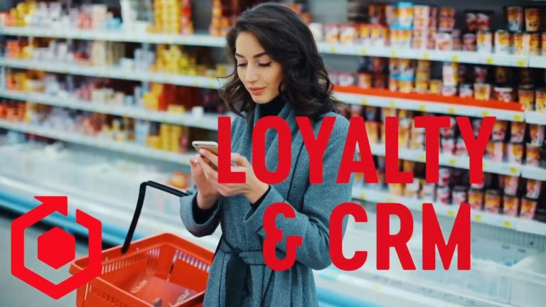 A women on the grocery store, scrolling through her phone. The title Loyalty & CRM displays across the screen