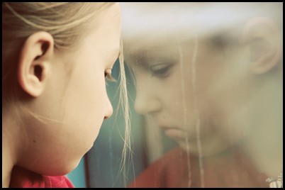 Little girl looking into window