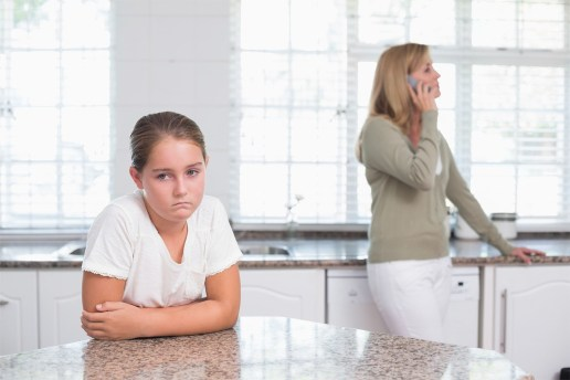 Mother on the phone while daughter sulking at home in the kitchen