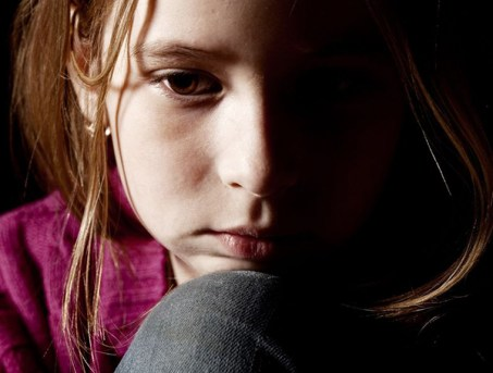 13472601 - sad child on black background. portrait depression girl