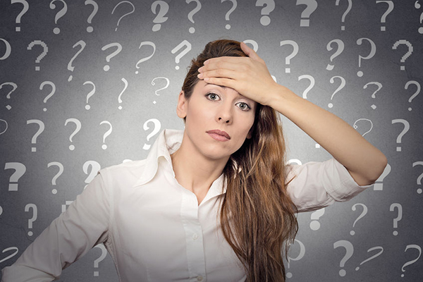 32551869 - portrait stressed woman with headache has many questions isolated grey wall background with question marks.