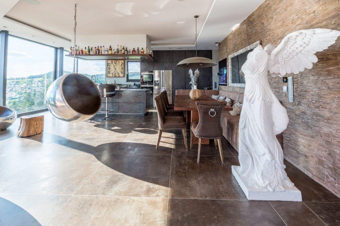 Eyecatcher Lounge Ball und kopfloser Engel neben Live-Edge Tisch und Eckbankkombination