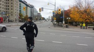 An armed officer walking toward the shooting scene