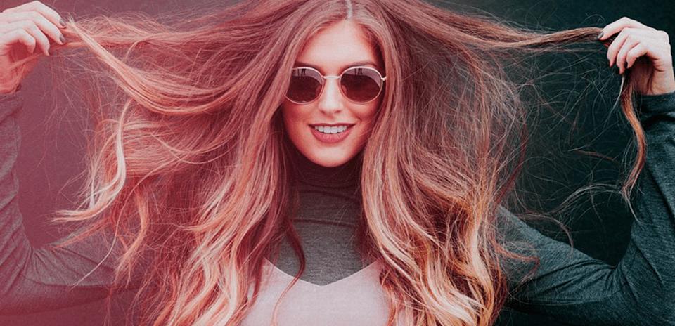 Uma mulher de óculos escuros, segurando o cabelo com as duas mãos, colocando os cabelos no ar. E um parque de fundo.