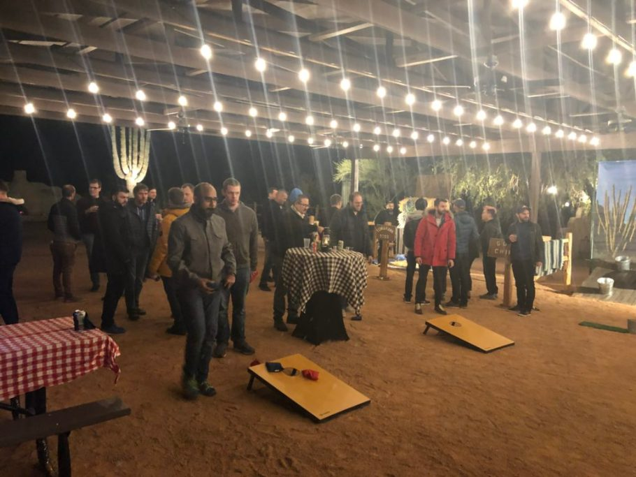Developers play cornhole under a well lit awning