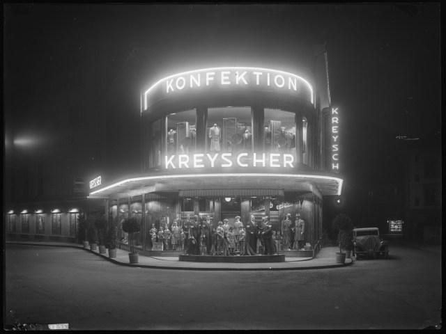 q-12-1-1295-baden-ecke-bahnhofstrasse-hirschlistrasse-konfektionsgeschaft-kreyscher-mit-neuem-halbrundem-anbau-nachtaufnahme-1931-1931