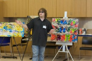 John Bramblitt talking about his works of art to summer campers